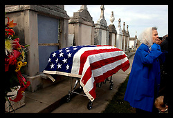 9th December, 2005. Aftermath of Hurricane Katrina, New Orleans, Louisiana. 3 1/2 months after the storm, New Orleans continues to bury the victims. 77 year old widow Geneva and family at the funeral of her husband Vincent Giuffre at Greenwood cemetery. 87 year old Guiffre died in the arms of his 77 yr old wife Geneva in New Orleans East as the flood waters swirled aroud their kitchen. Geneva placed her cat Patsy in her attic, fully expecting her beloved pet to die. She swam out of her back door, leaving her husband's body floating in the kitchen. She held onto the drain surrounding her house roof and made her way to the front of the building where she clung on to the drainpipe for 3 days. Geneva was rescued by helicopter, taken to Houston. Her frantic family did not learn that she was safe for 4 days. The only thing she was able to save from her house was her wedding ring. Geneva and Vincent had been married 56 years. Miraculously a neighbour saved her cat, discovering it alive 3 weeks after the storm hit. Geneva and her cat now live with her son Gary in Atlanta.