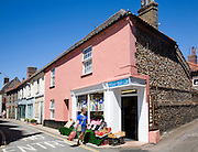 Small corner shop and historic buildings in the market town of Holt Norfolk England