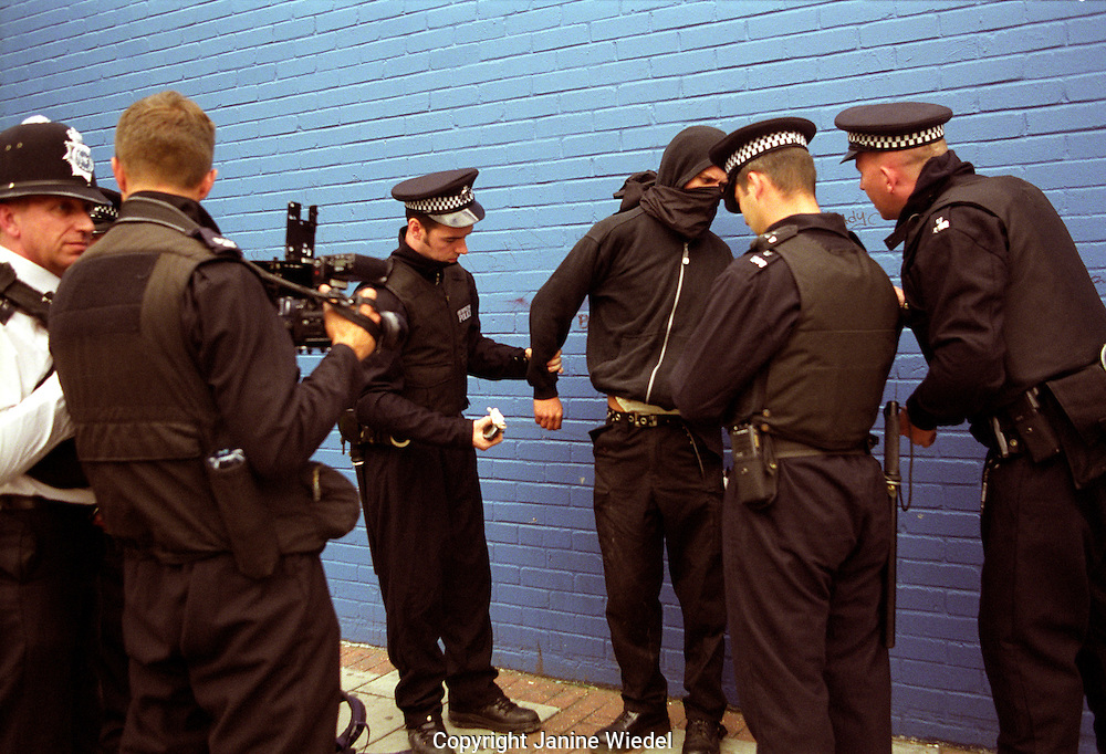 Young demonstrator being searched by police under section 44 at a 2003 arms trade Fair at Excel Center demonstration in London
