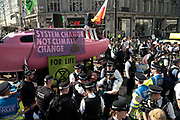 Climate protesters and Police at Oxford Circus. In an operation that took several hours, Police removed the pink boat named Berta Caceres after the Hondruan nun who was murdered for being an environmental activist, that was the centrepiece of Extinction Rebellions site. It involved people who were locked on being removed. Several roads were blocked across four sites in central London, by the Extinction Rebellion climate change protests, April 2019.