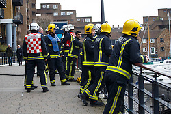 © Licensed to London News Pictures. 09/03/2015. LONDON, UK. Firefighters attending to a fire started on a 10 tonne motor yacht at St Katharine Docks in London on Monday, 9 March 2015. The middle deck of a motor yacht was destroyed by the blaze. Photo credit : Tolga Akmen/LNP