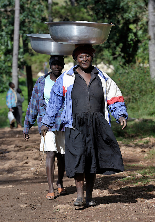 Carrying basins on their heads, women walking in the mountainous community of Foret-des-Pins, Haiti.