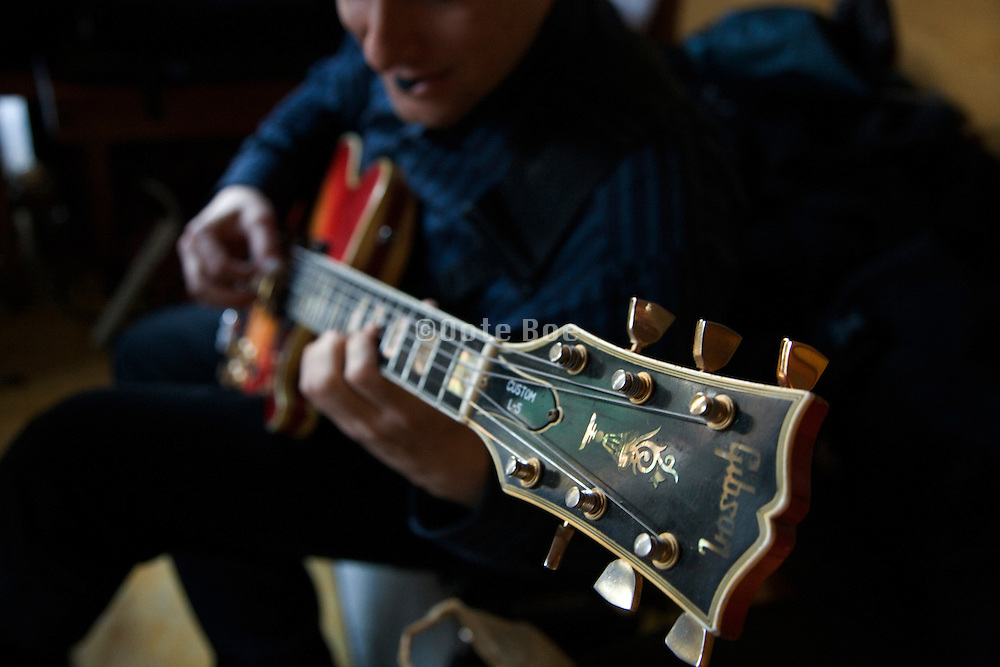 musician playing a Gibson custom electric guitar