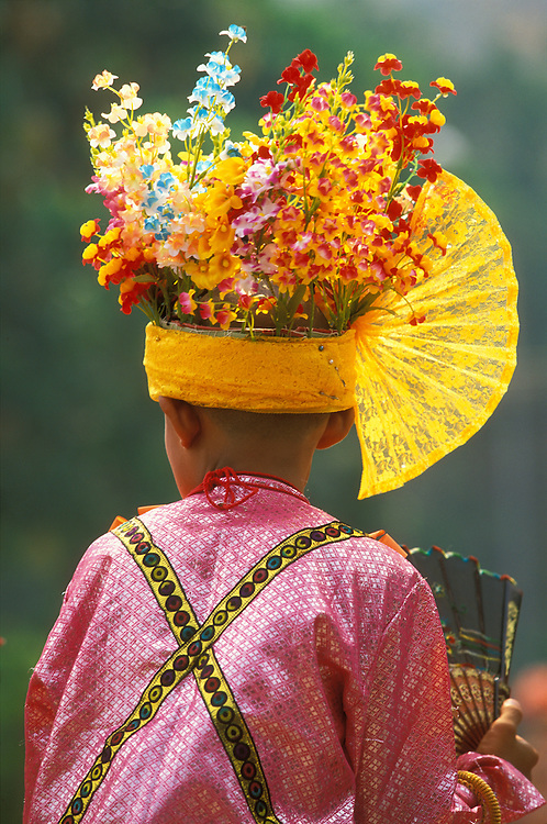 A boy dressed up as a prince rides on the shoulders of an attendant at Poy Sang Long, the yearly ordination of novice monks, Mae Hong Son, Thailand.