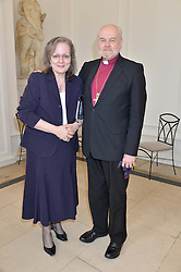 The Bishop of London RICHARD CHARTRES and his wife CAROLINE CHARTRES at a party to celebrate the 150th anniversary of Wartski held at The Orangery, Kensington Palace, London, on 19th May 2015.