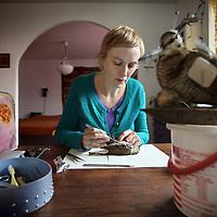 Nederland, Amsterdam , 7 oktober 2010..Mevrouw Seekes uit de Boomstraat is preparateur van vogels. .Op de foto is ze een dode lijster aan het prepareren. Op de voorgrond een geprepareerde opgezette snip..Taxidermist preparing a song-thrush to be stuffed. A snipe in the front.