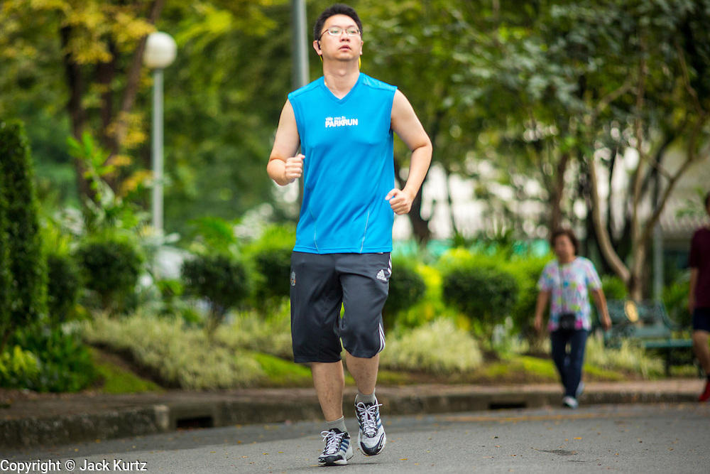 06 OCTOBER 2012 - BANGKOK, THAILAND: A jogger runs through Lumphini Park in Bangkok. The Thai government promotes exercise classes as a way staying healthy. Lumphini Park is 142 acre (57.6-hectare) park in Bangkok, Thailand. This park offers rare open public space, trees and playgrounds in the congested Thai capital. It contains an artificial lake where visitors can rent boats. Exercise classes and exercise clubs meet in the park for early morning workouts and paths around the park totalling approximately 1.55 miles (2.5 km) in length are a popular area for joggers. Cycling is only permitted during the day between the times of 5am to 3pm. Smoking is banned throughout smoking ban the park. The park was created in the 1920's and named after Lumbini, the birthplace of the Buddha in Nepal.   PHOTO BY JACK KURTZ
