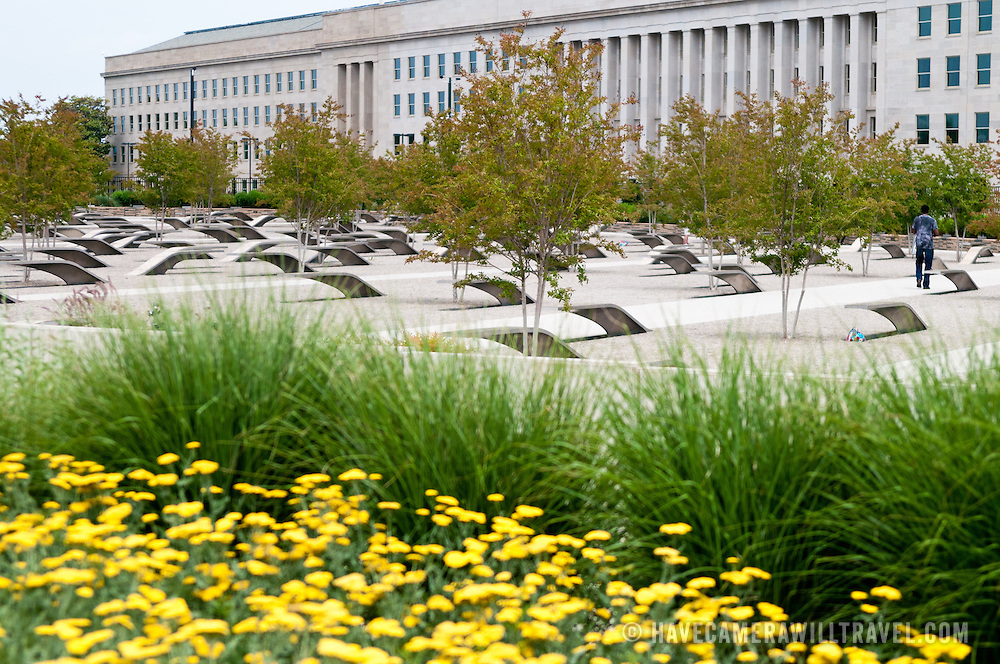 Yellow flowers in the foreground and the Pentagon building in the background of the Pentagon Memorial. The Pentagon Memorial is in remembrance of the events of September 11, 2001, and the 184 people who died as victims of the terrorist attack on the Pentagon. The Memorial is adjacent to the southwest side of the Pentagon. Designed by Julie Beckman and Keith Kaseman, the memorial opened to the public on September 11, 2008, it is designed with one illuminated for each victim of the attack, arranged by the person's age. Each bench has a small pond of water underneath, and a name is etched on the end of each bench.