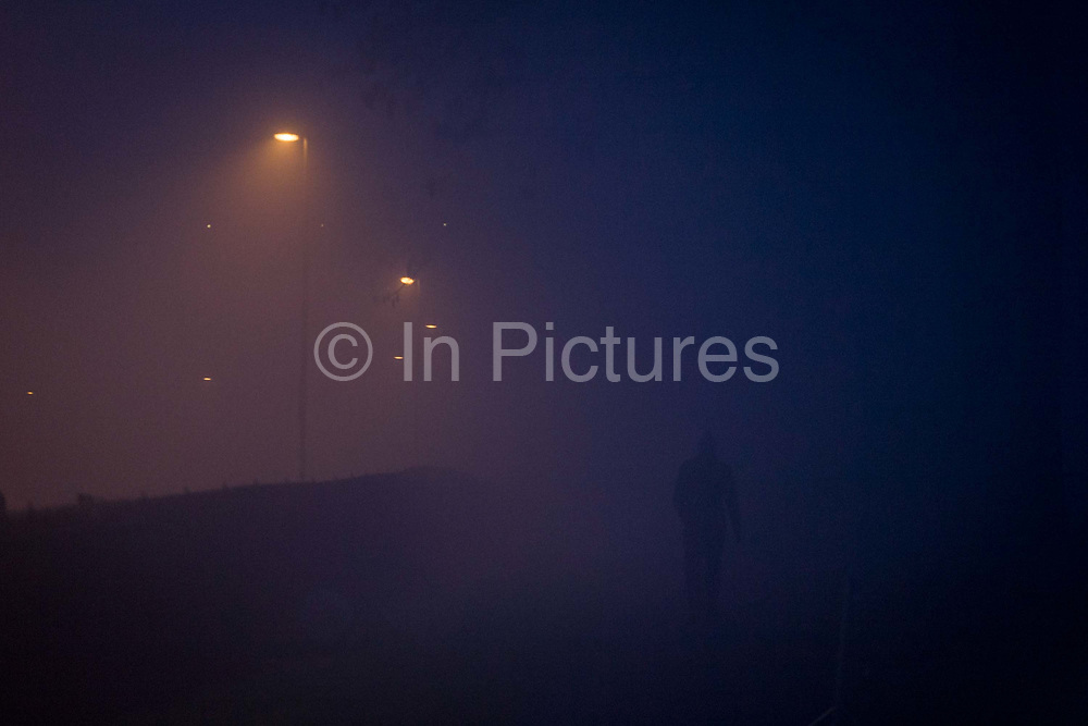 The silhouette of a figure walking through a park, with a foggy residential street in the background. The menacing figure looks ghostly, a menacing and eerie scene that seems to threaten the safety of approaching others. Freezing fog lies in the street in this south London suburb in the depths of mid-winter. We can't see his face or features and his ominous and sinister shape guarantees his anonymity.