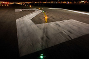 "A wide night view looking down on the rubber-stained of runway 27R at Heathrow Airport. During a time-exposure and partially-lit by the headlights and spotlights of an airfield emergency vehicle, we see the giant numbers 27 that landing pilots will see from a mile away as they descend towards the airport's threshold. The numbers relate to the compass bearing that the line of the runway takes: In this case 270 degrees from north and has a parallel southern twin. Across the number two we also see a set of taxiway lights that help the steering pilot navigate across the airfield and line-up on the departing runway. <br /> From writer Alain de Botton's book project ""A Week at the Airport: A Heathrow Diary"" (2009)."