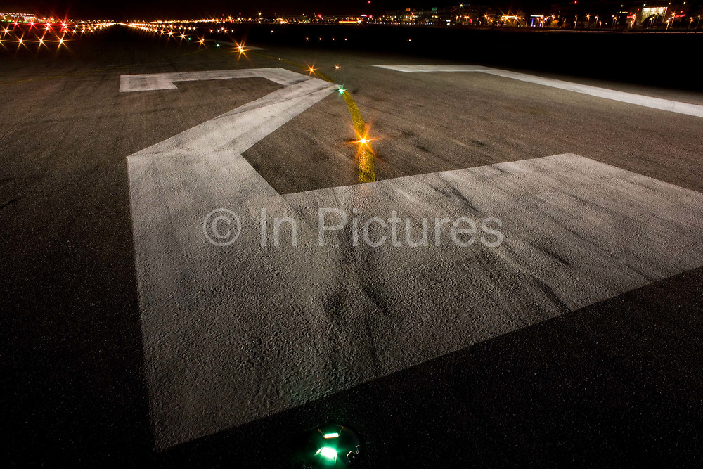 """A wide night view looking down on the rubber-stained of runway 27R at Heathrow Airport. During a time-exposure and partially-lit by the headlights and spotlights of an airfield emergency vehicle, we see the giant numbers 27 that landing pilots will see from a mile away as they descend towards the airport's threshold. The numbers relate to the compass bearing that the line of the runway takes: In this case 270 degrees from north and has a parallel southern twin. Across the number two we also see a set of taxiway lights that help the steering pilot navigate across the airfield and line-up on the departing runway. <br /> From writer Alain de Botton's book project """"A Week at the Airport: A Heathrow Diary"""" (2009)."""