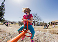 Kami Lamarre catches the warm spring breeze while on the see saw at Leavitt Park's playground on Sunday afternoon.  (Karen Bobotas/for the Laconia Daily Sun)