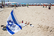 A woman rests  in the shade of the Israeli national flag during Independence Day celebrations in Tel-Aviv, Israel April 15, 2021. People gathered in their masses at Tel-Aviv's shore line as the Jewish state celebrates 73 years to it's establishment. As vast percentage of the population are vaccinated, celebrations were able to take place in a some what ordinary manner.Starting Sunday April 18, 2021, it will no longer be mandatory to wear a protective mask in open spaces throughout the country.