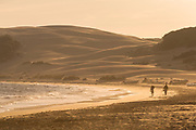 Silhouettes of men on Bolonia beach in Spain
