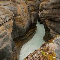 A hiker walks past dramatic Mistaya Canyon.