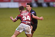 Elijah Taylor (13) of Salford Red Devils head in to the tackle of Greg O'Neill