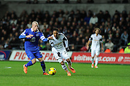 Jonathan De Guzman of Swansea city breaks away from Everton's Ross Barkley (l). Barclays Premier league, Swansea city v Everton at the Liberty Stadium in Swansea,  South Wales on Sunday 22nd Dec 2013. pic by Andrew Orchard, Andrew Orchard sports photography.