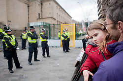 """demonstrator with young child leans against """"the ring of steel""""  and watches police in  Barkers Pool, outside Sheffield city Hall where the Liberal Democrats are holding their Party conference Conference Sheffield Saturday.12 March 2011.Images © Paul David Drabble"""
