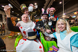 "Mr Martini's booth with the Mad Hatter, Alice, the White Rabbit and King of hearts in their Alice in Wonderland ""Through the Looking Glass"" theme during the Motor Bike Expo. Verona, Italy. January 24, 2016.  Photography ©2016 Michael Lichter."