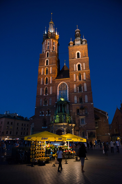 People walk at night in the Main Market Square (Rynek Glowny Square) in Krakow, Poland. The 262-foot tall building is the Church of Our Lady Assumed into Heaven, also called St. Mary's Church, a Gothic church re-built in the 14th century.