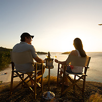 A couple enjoy champagne on ice from a rock with a view at Lizard Island resort, far north Queensland, Australia.