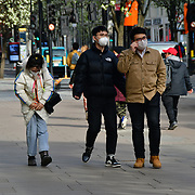 Three Chinese from China say, If you care weak a mask, and they say the westerners mentality think is a flu in fact is more then a flu at Oxford Circus underground people sitting inside the tube wearing mask on 21 March 2020, UK.