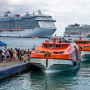 North America, Caribbean, Cayman Islands, Cayman, Grand Cayman, Georgetown, <br /> Transfering between a massive cruise ship and a small craft in Georgetown harbor, Grand Cayman.
