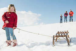 Girl with sledge, family standing in background, Bavaria, Germany