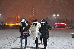 January 3, 2018 - Xi'An, China - Girls in heavy jackets brace the first snow of New Year in Xi'an, northwest China's Shaanxi Province. (Credit Image: © SIPA Asia via ZUMA Wire)
