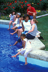 Stock photo of a group of people dipping their feet in a cool pool in the afternoon