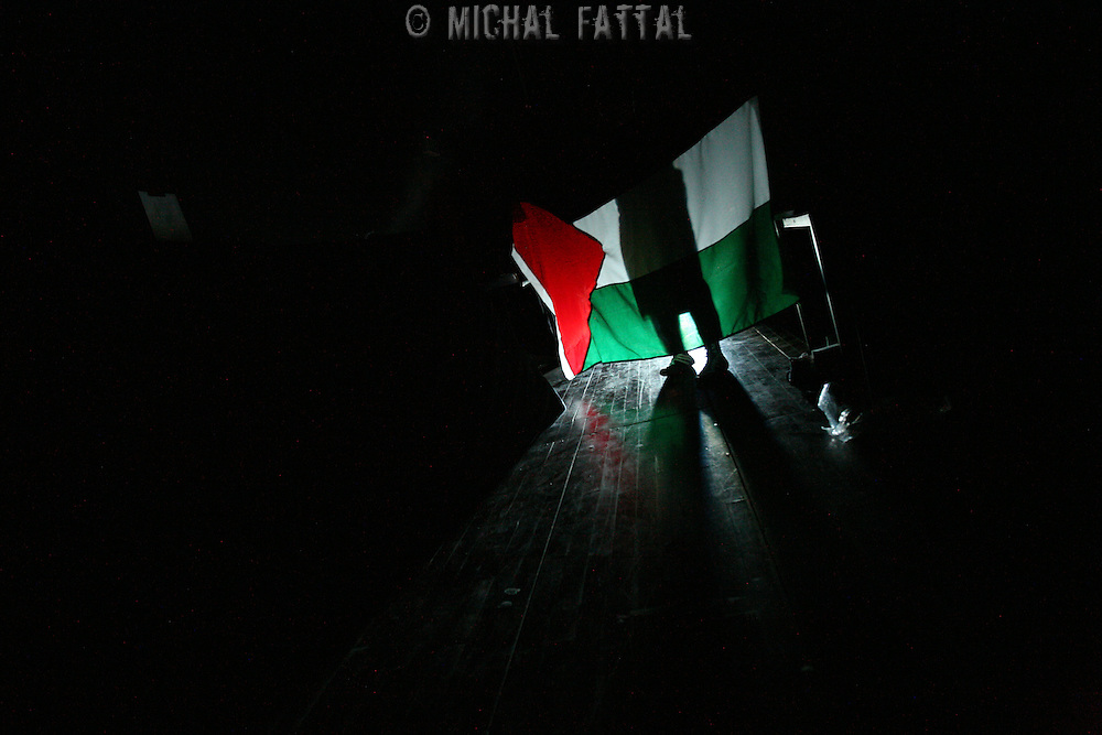"""A Member of The Palestinian Circus School holds up a Palstinian flag behind the scenes, before going on stage to perform the show """"Circus behind the wall"""" in Ramallah, November 20, 2009.The circus group was established in 2006, in order to give a new way of expression for Palestinians, and a new way to deliver the idea of resistance to the occupation. This performance is based on the life of Palestinians behind the separation wall. Photo by Michal Fattal/backyard"""