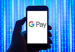 Person holding smart phone with  Google Pay  logo displayed on the screen. EDITORIAL USE ONLY