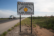 Welcome sign to Eddy County New Mexico with oil industry installations on the horizon. <br /> Eddy County's oil patch in the Permian Basin is experiencing an oil boom due to the fracking industry.