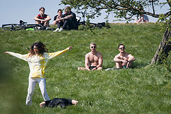 © Licensed to London News Pictures. 15/04/2020. London, UK. Members of the public sunbathing and exercising on Primrose Hill, North London, during a pandemic outbreak of the Coronavirus COVID-19 disease. The public have been told they can only leave their homes when absolutely essential, in an attempt to fight the spread of coronavirus COVID-19 disease. Photo credit: Ben Cawthra/LNP