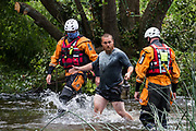 Police officers from Hampshire Police Marine Support Unit move a male environmental activist from HS2 Rebellion away from an ancient alder tree which he had been trying to protect from destruction during works for the HS2 high-speed rail link on 24th July 2020 in Denham, United Kingdom. A large security operation involving officers from the Metropolitan Police, Thames Valley Police, City of London Police and Hampshire Police as well as the National Eviction Team ensured the removal of the tree by HS2 despite the protests by activists.
