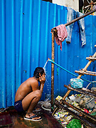 """12 FEBRUARY 2019 - SIHANOUKVILLE, CAMBODIA:  A Cambodian construction worker bathes at a public water spigot outside the the Blue Bay casino and resort development under construction in Sihanoukville. There are about 50 Chinese casinos and resort hotels either open or under construction in Sihanoukville. The casinos are changing the city, once a sleepy port on Southeast Asia's """"backpacker trail"""" into a booming city. The change is coming with a cost though. Many Cambodian residents of Sihanoukville  have lost their homes to make way for the casinos and the jobs are going to Chinese workers, brought in to build casinos and work in the casinos.     PHOTO BY JACK KURTZ"""
