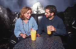 Young couple sitting at table in bar drinking orange juice and talking,