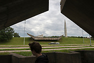 Tallinn, Estonia - July 28, 2015: A young man and two cars pass the Maarjamäe Memorial, a war memorial to Soviet soldiers who died in World War II, in Tallinn, Estonia.