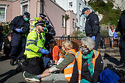 Police start to remove activists from Insulate Britain who have blockaded the entrance to the port of Dover on the 24th of September 2021 in Dover, United Kingdom. Over 40 activists from Insulate Britain blocked the road with some gluing themselves to the carriageway of the A20 at the Eastern docks roundabout. There are blocking the roads to highlight that fuel poverty is killing people in Dover and across the UK.