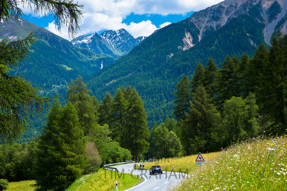 Car overtaking cyclists on touring holiday in the Swiss Alps, Swiss National Park, Switzerland