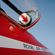 A flying helmet belonging to a member of the elite 'Red Arrows', Britain's prestigious Royal Air Force aerobatic team, is cradled in the highly-polished open Plexiglass  canopy of a team Hawk jet aircraft. With the arrow pointing downwards we see it from below along with the airplane's red fuselage and the words Royal Air Force stencilled in blue lettering on the side within a white stripe. There are strong angles with clear blue space on the top right. The colours that dominate this image are red, white and blue - the colors of the Union Jack, United Kingdom's flag. This scene is at RAF Akrotiri, Cypus where the Red Arrows put the finishing touches to their display sequences before starting the gruelling air show calendar in the UK and Europe. The squadron represents all that is perfect with aerobatic flying, about teamwork and discipline.