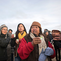 Beatrice Menasekwe walks through camp handing out water during the morning water ceremony in Standing Rock, ND Tuesday.