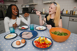 Black girl and white girl eating meal