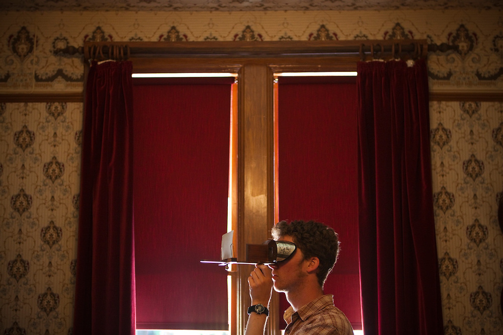 Zach Podell-Eberhardt looks through an antique stereoscope inside the Helmcken House at the Royal BC Museum in Victoria, British Columbia, Canada.