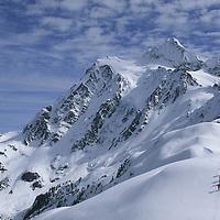 Skiers hike along Shukson Arm in Mt. Baker Wilderness, Mt. Shuksan bkg.