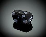 Cutout of a snowflake obsidian gemstone on black background