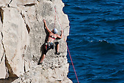 A rock climber scales the cliff face at Hedbury quarry on the Purbeck coast, Dorset, UK