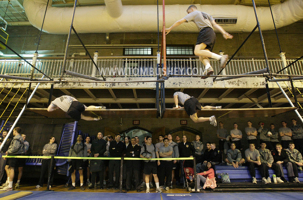"""One cadet, at top right, walks across the horizontal """"H"""" bars as two other cadets, complete the shelf mount obstacle during the Indoor Obstacle Course Test in Hayes Gym at the U.S. Military Academy at West Point on Feb. 9, 2010."""