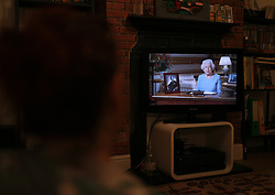 A woman watches a pre-recorded speech by Queen Elizabeth II on television in London, to mark the 75th anniversary of VE Day.