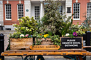 An old decorated porters wagon with a coronavirus distancing sign in a deserted Covent Garden, on 3rd March 2021, in London, United Kingdom. All non-essential shops and resturants are closed in the capitals West End during the third lockdown of the Coronavirus pandemic.